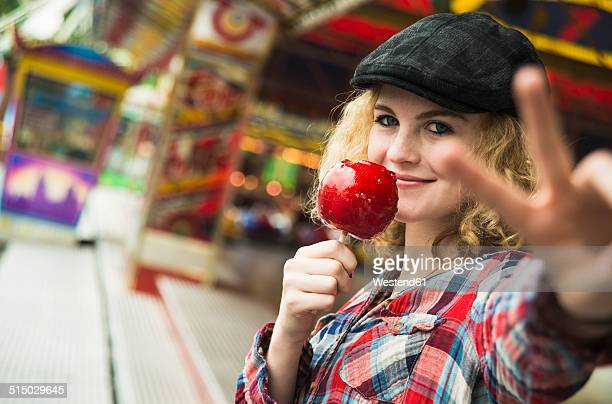 Portrait of happy teenage girl with candied apple showing victory-sign