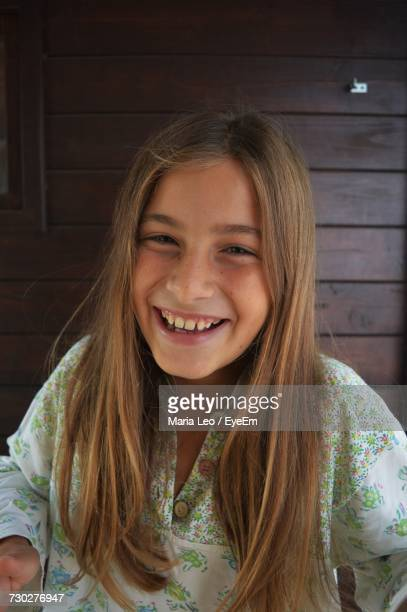 Portrait Of Happy Teenage Girl With Long Hair Against Wooden Wall