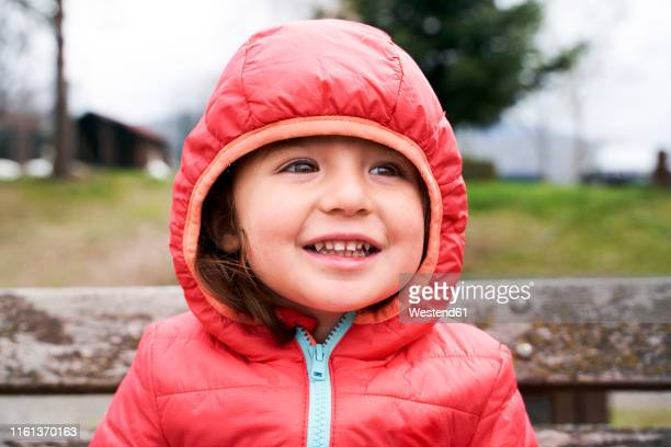 portrait of happy toddler girl wearing red down jacket with hood - padded jacket stock pictures, royalty-free photos & images
