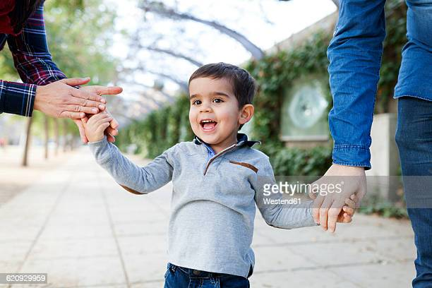 Portrait of happy toddler walking hand in hand with his parents