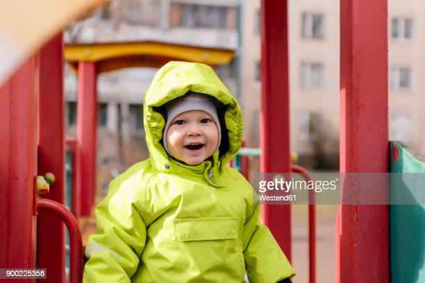 Portrait of happy toddler with rain jacket on playground
