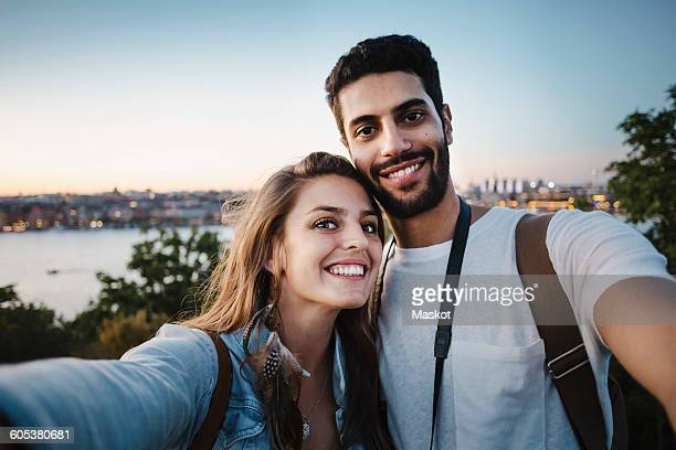 portrait of happy tourist couple against clear sky - selfie stock pictures, royalty-free photos & images