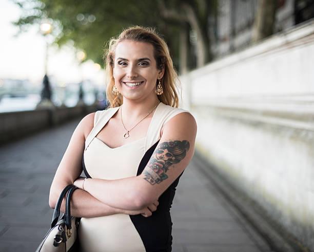 Portrait of happy transgender female with handbag and tattoo
