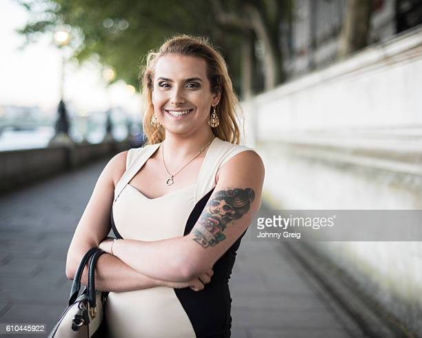 Portrait of happy transgender female with handbag and tattoo
