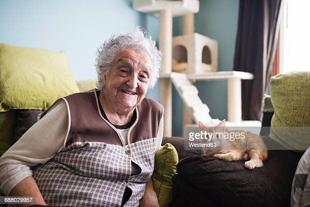 Portrait of happy woman and her cat sitting on couch in the living room