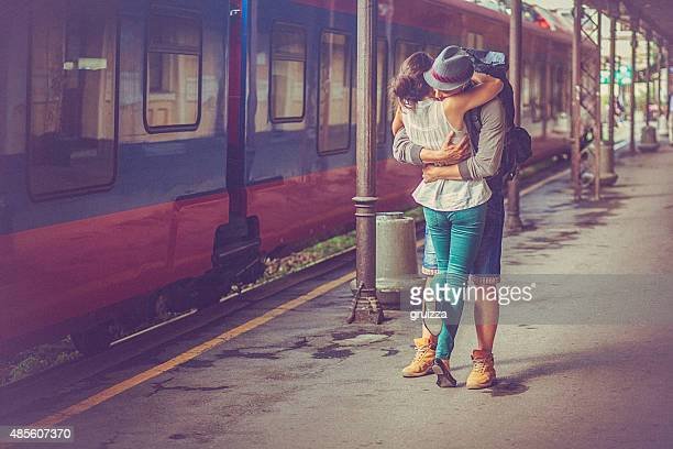 Portrait of happy woman and man embracing at railway platform