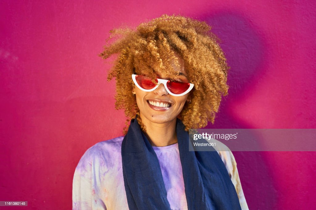 Portrait of happy woman before a pink wall : Stock Photo