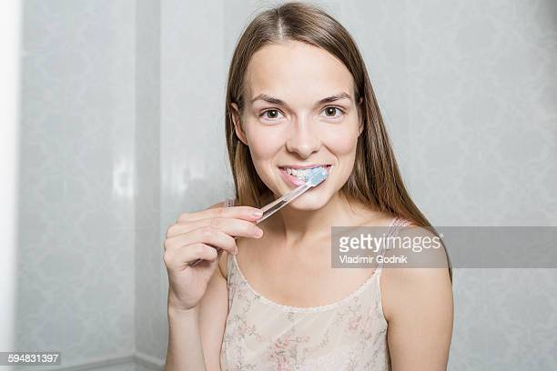 Portrait of happy woman brushing teeth in domestic bathroom
