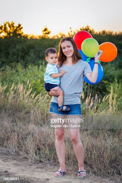 Portrait Of Happy Woman Carrying Son And Balloons On Field