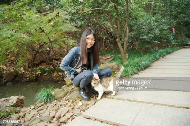 Portrait Of Happy Woman Crouching By Stray Cat On Footpath At Park