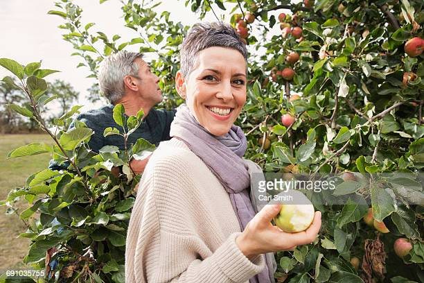 Portrait of happy woman eating apple in orchard