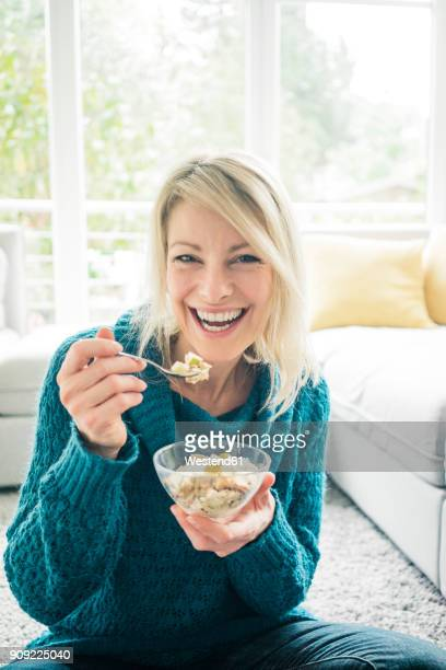 portrait of happy woman eating fruit muesli in living room - essen mund benutzen stock-fotos und bilder