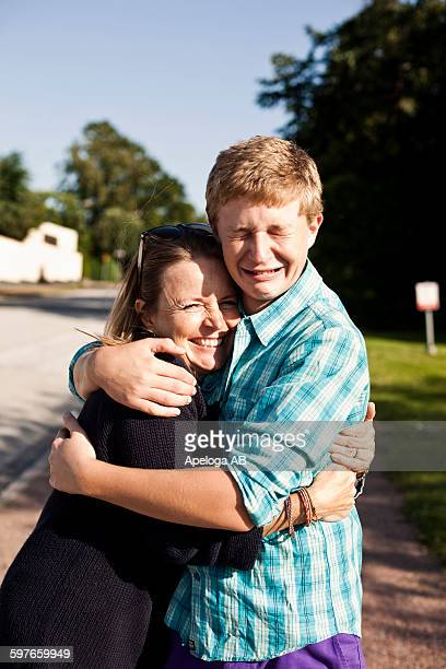 Portrait of happy woman embracing crying son