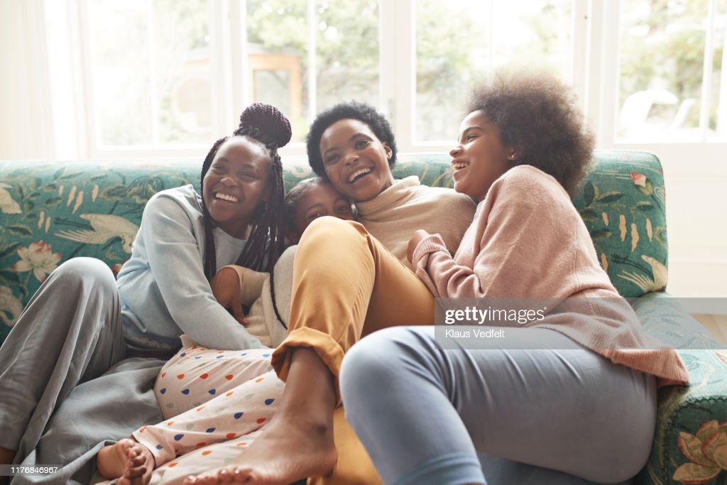 Portrait of happy woman embracing girls at home : Photo