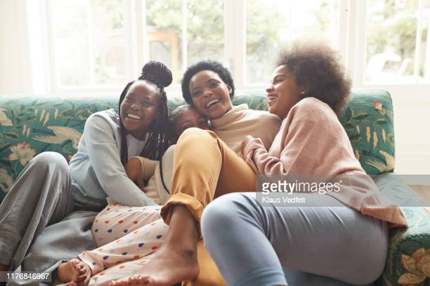 portrait of happy woman embracing girls at home - d'origine africaine photos et images de collection