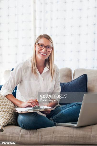 Portrait of happy woman holding clipboard while sitting on sofa at home