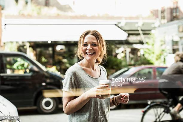 Portrait of happy woman holding disposable coffee cup on street