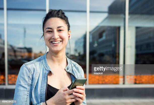 Portrait of happy woman holding mobile phone in city