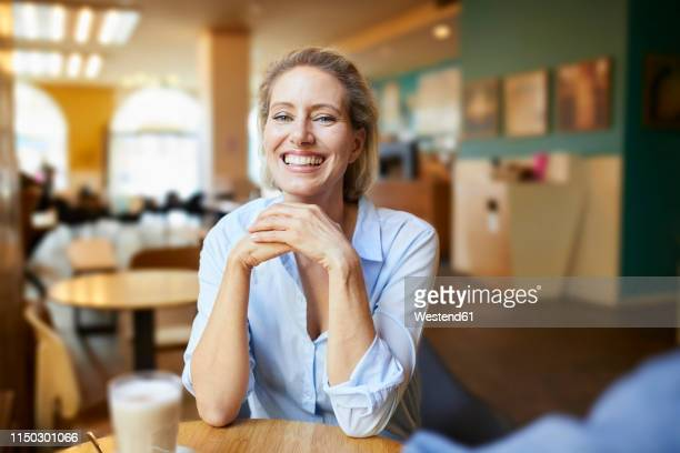portrait of happy woman in a cafe - blouse stockfoto's en -beelden