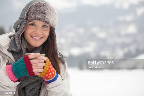 Portrait of happy woman in fur hat drinking coffee in snowy field