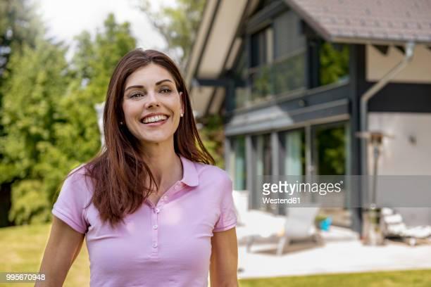 Portrait of happy woman in garden of her home