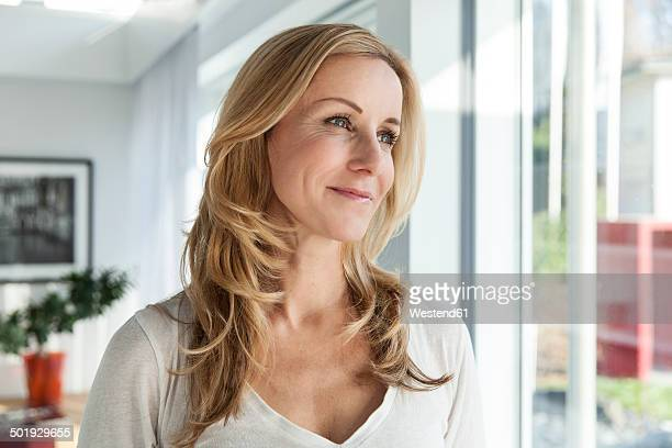 Portrait of happy woman in her bright modern home
