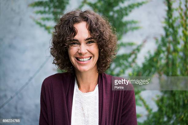 Portrait of happy woman is standing against wall