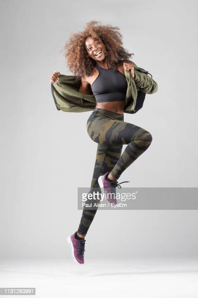 portrait of happy woman jumping against gray background - aikāne stock pictures, royalty-free photos & images