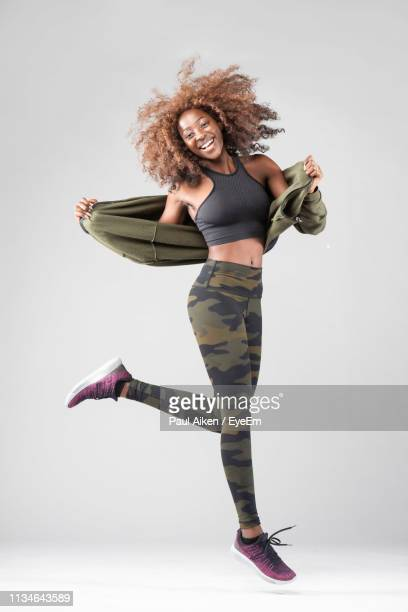portrait of happy woman jumping against gray background - black jacket stock pictures, royalty-free photos & images