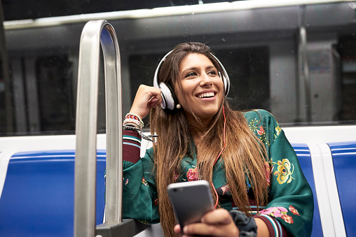 Portrait of happy woman listening music with headphones and smartphone in underground train - gettyimageskorea