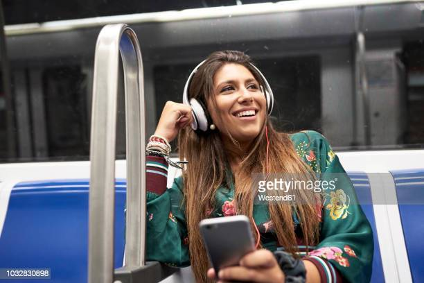 portrait of happy woman listening music with headphones and smartphone in underground train - listening stock pictures, royalty-free photos & images