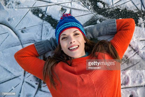 Portrait of happy woman lying down on frozen lake surface
