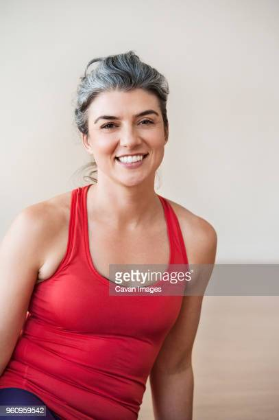 Portrait of happy woman performing yoga in gym
