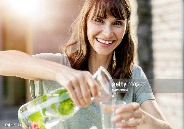 portrait of happy woman pouring infused water into glass - infused water stock pictures, royalty-free photos & images