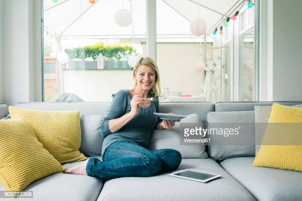 Portrait of happy woman relaxing on couch