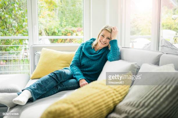 portrait of happy woman relaxing on couch - cushion stock photos and pictures