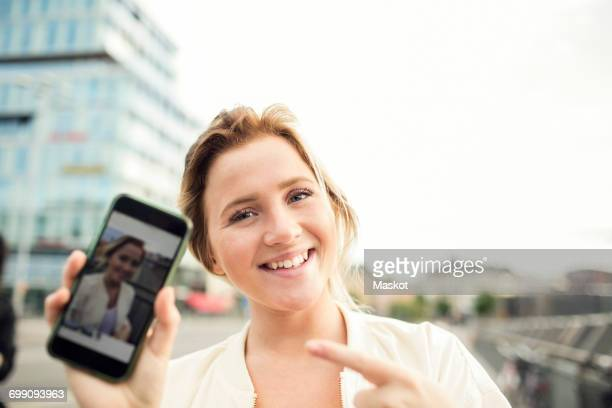portrait of happy woman showing photograph in mobile phone - mit dem finger zeigen stock-fotos und bilder