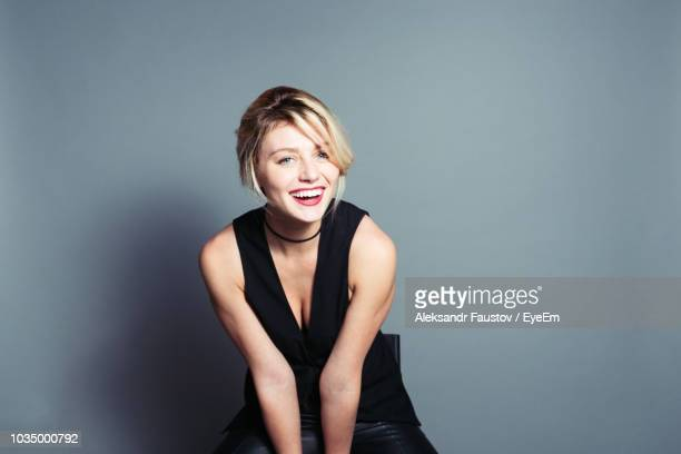 portrait of happy woman sitting against gray background - jeune femme blonde photos et images de collection