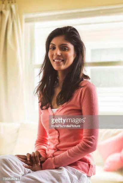Portrait of happy woman sitting at window