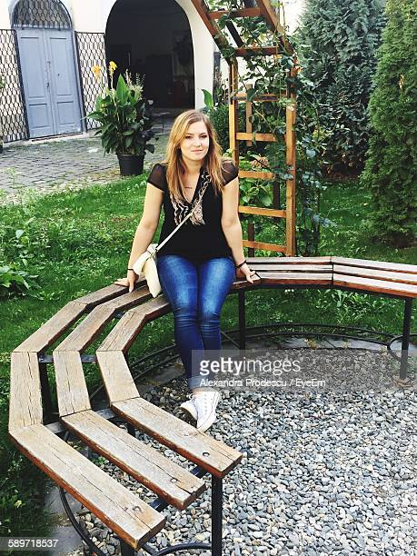 Portrait Of Happy Woman Sitting On Bench At Park