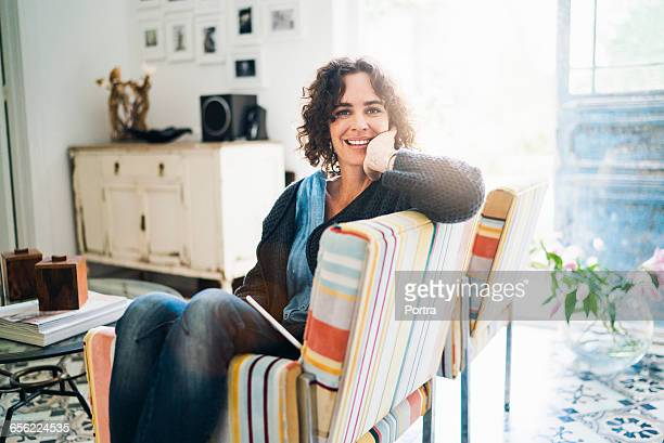 Portrait of happy woman sitting on chair at home