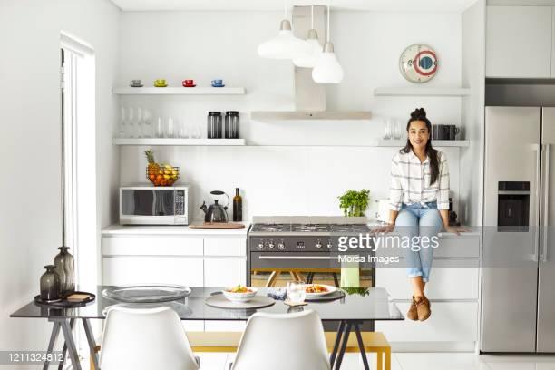verticale de femme heureuse s'asseyant sur le comptoir de cuisine - four people photos et images de collection