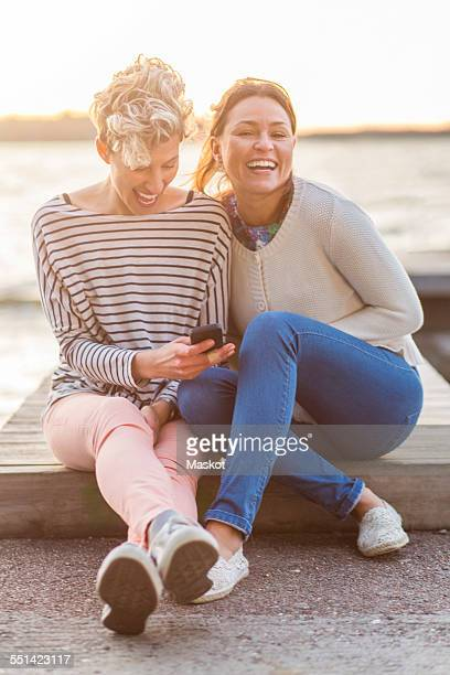portrait of happy woman sitting with female friend using mobile phone on pier - 30 39 años fotografías e imágenes de stock
