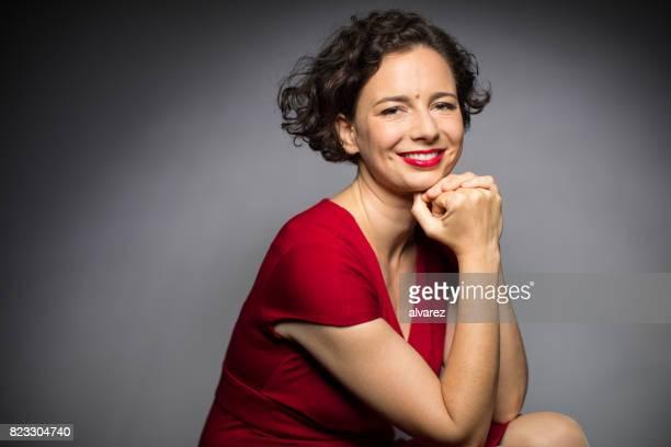 Retrato de mulher feliz sentado com a mão no queixo