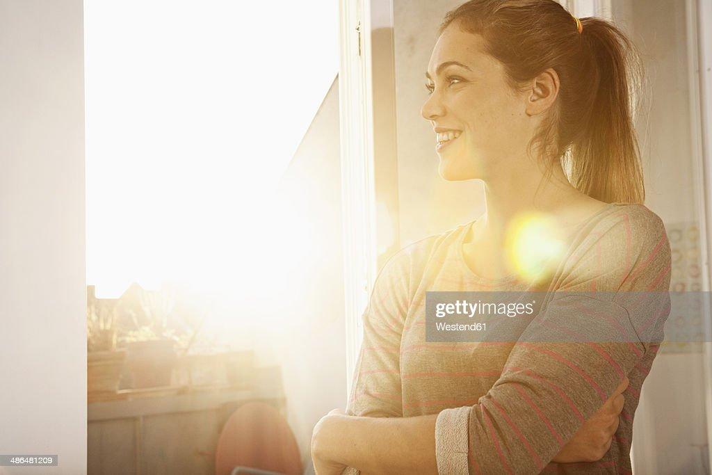 Portrait of happy woman standing at open window : Stock-Foto