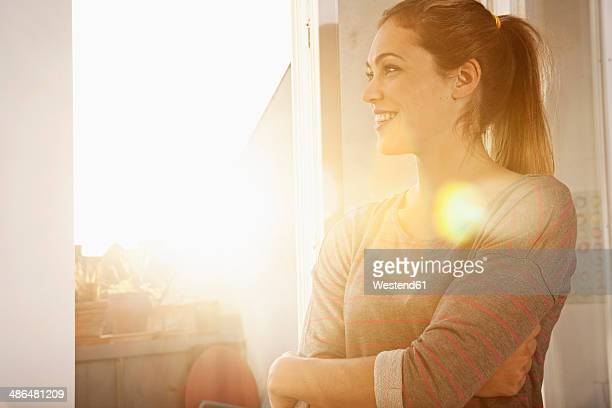 portrait of happy woman standing at open window - stralende lach stockfoto's en -beelden