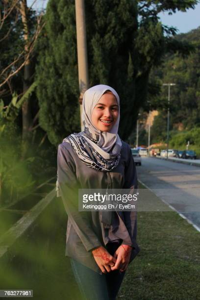 portrait of happy woman standing at roadside - kuantan stock pictures, royalty-free photos & images