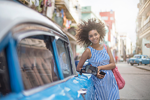 Portrait of happy woman standing by taxi in city - gettyimageskorea