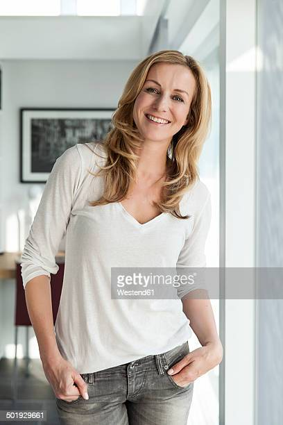 Portrait of happy woman standing in her bright modern home