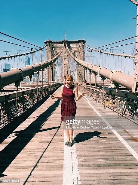 Portrait Of Happy Woman Standing On Brooklyn Bridge During Sunny Day